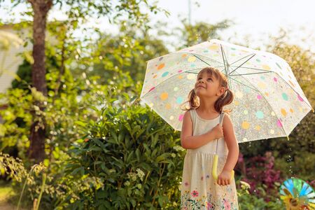 Little girl with an umbrella looks at the sky. Beautiful girl in garden under the summer rain. Vacation in village. Banque d'images