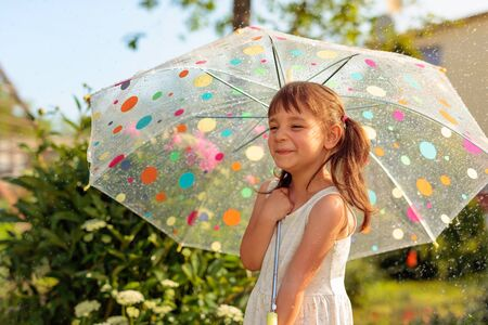Happy little girl with umbrella. Beautiful girl in garden under the summer rain. Vacation in village. Banque d'images