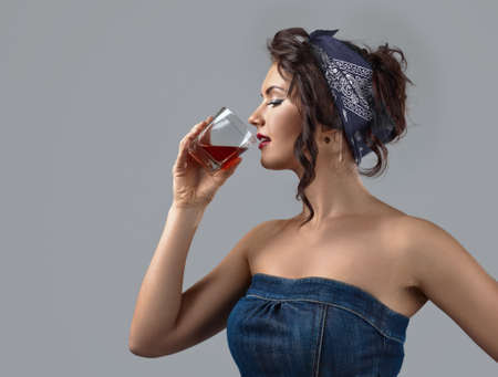 Beautiful young woman in a denim jumpsuit drinks whiskey. Portrait of a young brunette with wavy hair tied with a blue head kerchief. Copy space.