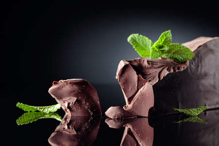 Large piece of bitter chocolate with mint on a black reflective background. Copy space.