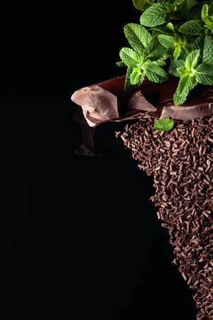 Pieces of dark bitter chocolate and chocolate chips with mint on a black reflective background. Copy space. Top view.