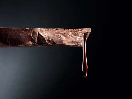 Melting piece of dark chocolate on a black background. Copy space.