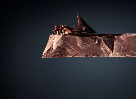 Large piece of dark chocolate and chocolate crumbs on a black background. Copy space. Reklamní fotografie