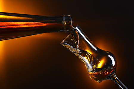 Pouring alcoholic drink into a glass on dark background.