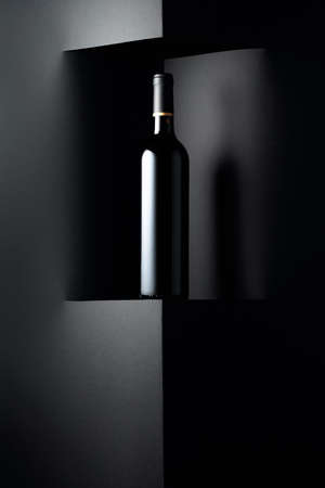 Unopened bottle of red wine on a black background. Copy space for your text.