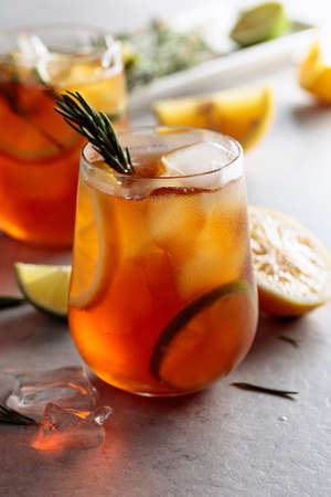 Traditional iced tea with lemon, lime and ice garnished with rosemary twigs. Frozen glasses with citrus slices.