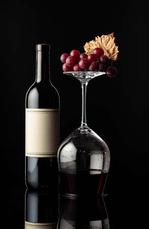 Bottle of red wine and an inverted wine glass with wine on a black background. Wine with grapes and dried vine leaves. There's an old empty label on the bottle. Concept of winemaking.
