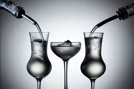 Vodka is poured from bottles into glasses with ice.