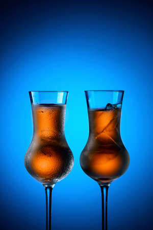Strong alcoholic drinks in dammed glasses with ice on a blue background. Copy space.