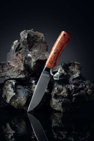 Hunter knife and broken stones. The blade has a beautiful damask pattern, handle - titan and elm.