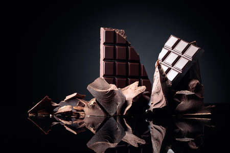 A broken chocolate bar and pieces of dark chocolate on a black reflective background. Copy space.