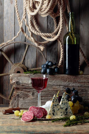 Rustic still life with red wine and snacks. On an old wooden table wine, blue cheese, dry-cured sausage, grapes, and rosemary. Simple and tasty food.