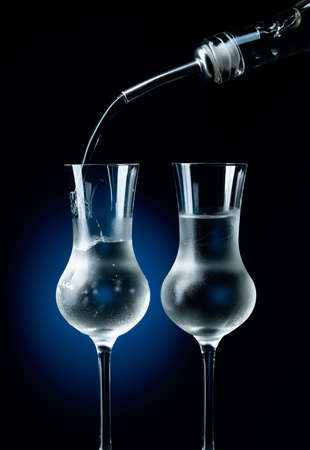 Vodka is poured from bottle into glass with ice.