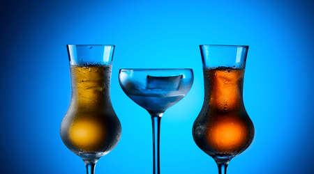 Strong alcoholic drinks in dammed glasses with ice on a blue background.