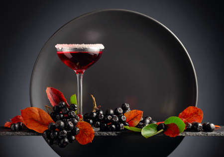 Black chokeberry (aronia melanocarpa) with juice or syrup. Fresh berries with leaves on a black background. Copy space. Zdjęcie Seryjne