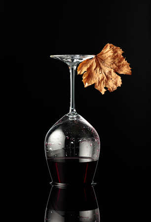 Inverted wine glass with red wine on a black reflective background. Wine and dried vine leaf. Concept of winemaking.