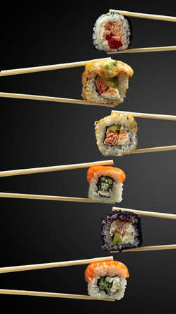 Fresh tasty sushi in wooden chopsticks on a dark background. Copy space. Banque d'images