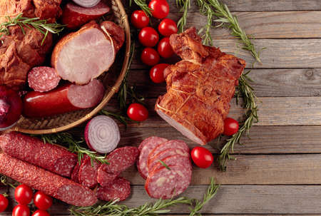 Food tray with delicious salami, ham, fresh sausages, tomato, and rosemary. Meat platter with a selection. Copy space.