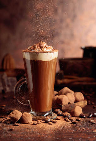 Truffles and glass of hot chocolate with whipped cream. Sweets and drink sprinkled with cocoa powder on an old brown table.