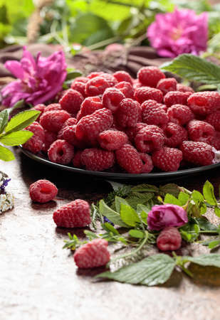 Fresh juicy raspberries on a black plate. Summer still life with, raspberries, flowers and meadow grasses.