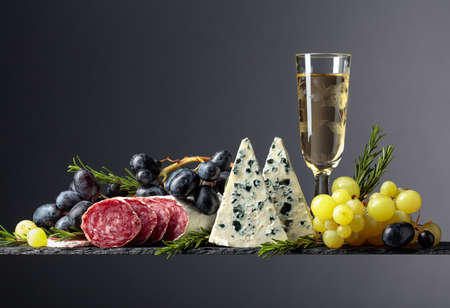 White wine and snacks on a black background. Glass of wine, blue cheese, dry-cured sausage, grapes, and rosemary. Simple and tasty food. Copy space.