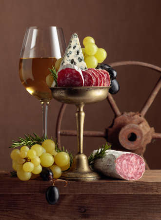 Glass of wine with snacks on a brown background. Wine, blue cheese, dry-cured sausage, grapes, and rosemary on an old wooden table. Simple and tasty food. Copy space. 版權商用圖片