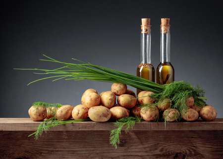 Young fresh organic potatoes with vegetable oil, dill and onion on a old wooden table. Copy space. 免版税图像