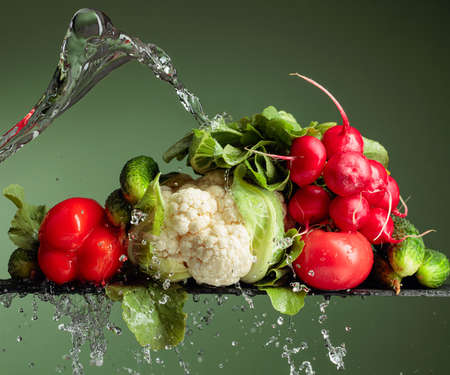 Various raw vegetables with water splash. Cauliflower, tomato, cucumber, radish and paprika on a green background.