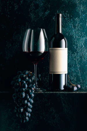Red wine and blue grapes on an old dark blue background. On a bottle old empty label. Copy space.