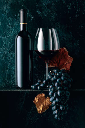 Red wine and blue grapes with dried up vine leaves on an old dark blue background. Copy space. 写真素材