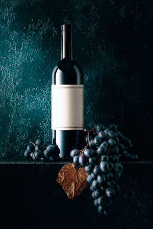 Bottle of red wine with the old empty label. Red wine and blue grapes with dried up vine leaves on an old dark blue background. Copy space. 写真素材