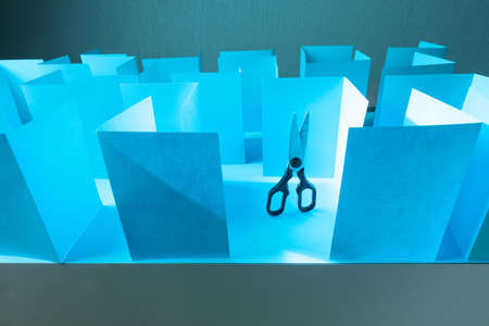 Scissors in blue paper labyrinth. Concept of theme of bureaucracy.