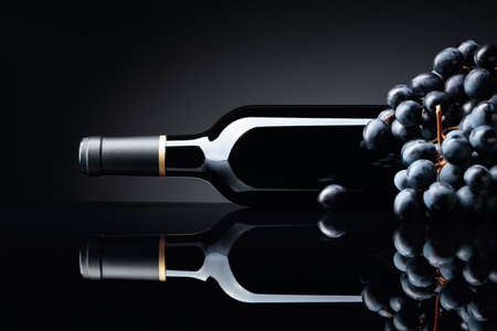 Bottle of red wine and a bunch of grapes on a black reflective background. Selective focus, copy space.