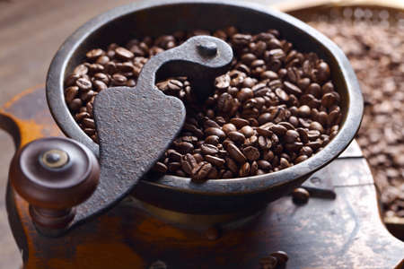 Roasted coffee beans in an old coffee grinder. Selective focus.