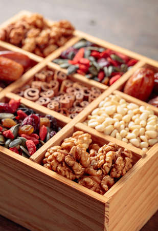 Dried fruits, various nuts and seeds in old wooden box. Selective focus.