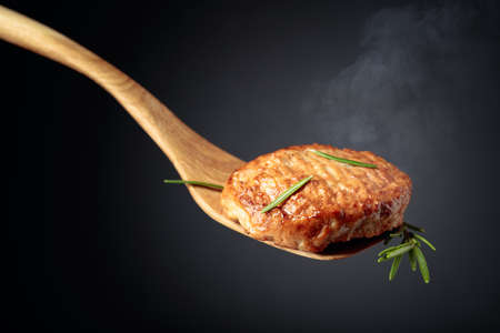 Delicious homemade cutlet with rosemary on a black background.