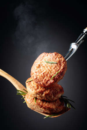 Delicious hot homemade cutlets with rosemary on a black background. Copy space.