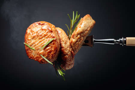 Delicious homemade cutlets with rosemary on a black background.