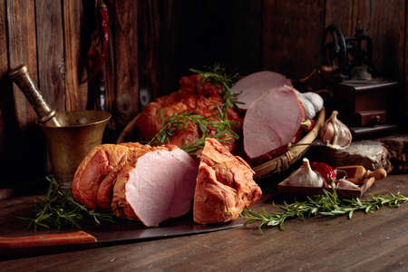 Smoked ham with herbs, spices, and kitchen utensils on an old wooden table.