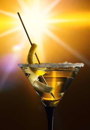 Dirty martini with a lemon twist on a yellow background.