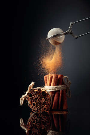 Cinnamon powder is poured out of the strainer. The ground cinnamon, cinnamon sticks, tied with jute rope on a black reflective background. Archivio Fotografico