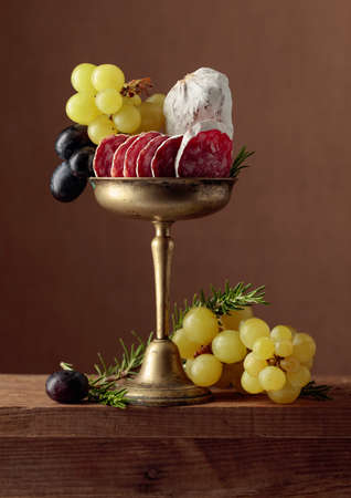 Dry-cured sausage, grapes, and rosemary on an old wooden table.