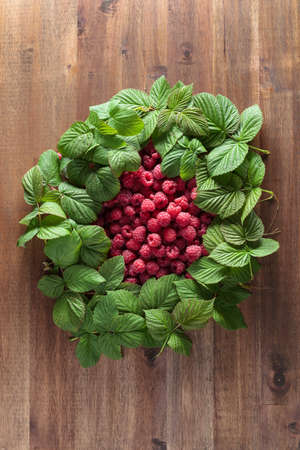 Ripe juicy red raspberries with green leaves on an old wooden table. Stock Photo