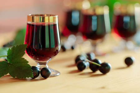 Homemade black currant liqueur and fresh berries. Stock Photo