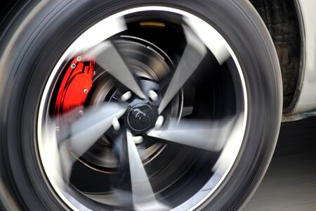 Red brake calipers on a fast-moving car Stock Photo
