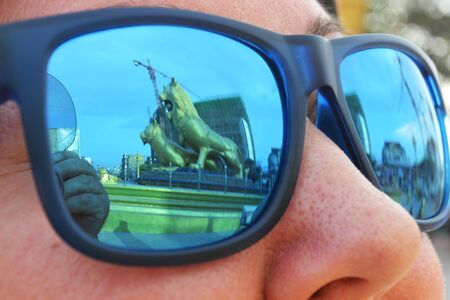 Closeup beautiful blue green mirrored sunglasses ultraviolet, sunshine at sunset, reflection monument Golden Lion, on face of girl. Concept fashion shooting accessories for optics store