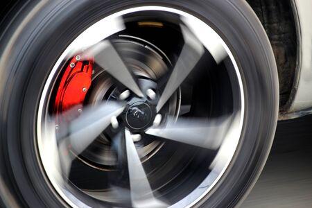 Red brake calipers on a fast-moving car Reklamní fotografie