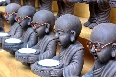 Sculptures of seated Buddha disciples with glasses, holding candles, gray, market, Siem Reap, Cambodia
