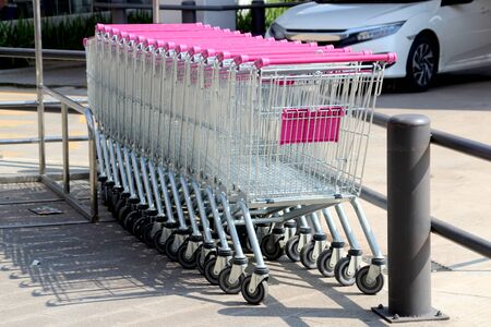 A row of supermarket trolleys with pink handles