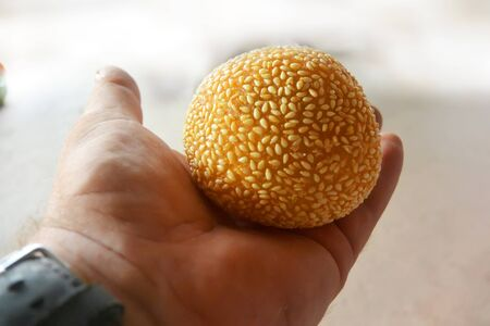 Hollow spherical donut sprinkled with sesame seeds in the palm of your hand